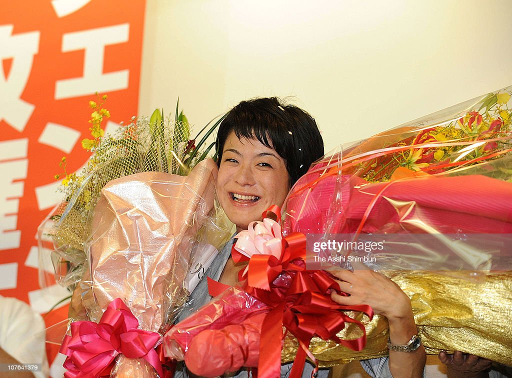 Newly elected lawmaker Eriko Fukuda smiles with flower bunches after winning in the Nagasaki No.2 Single Seat Constituency during the lower house election at his election campaign headquarters on August 30, 2009 in Isahaya, Nagasaki, Japan.