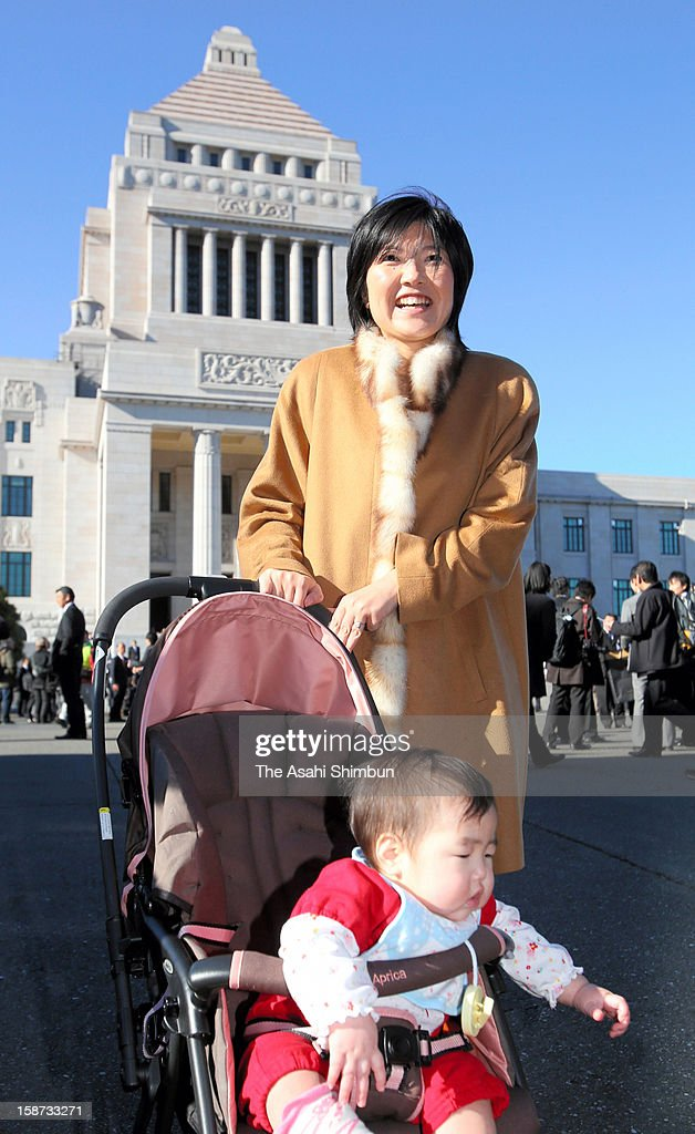 Newly elected lower house lawmaker Miyo Okubo of Liberal Democratic Party poses for photographs with her daughter at the diet building on December 26, 2012 in Tokyo, Japan. Liberal Democratic Party president Shinzo Abe becomes Japan's 96th prime minister, seventh in six years.