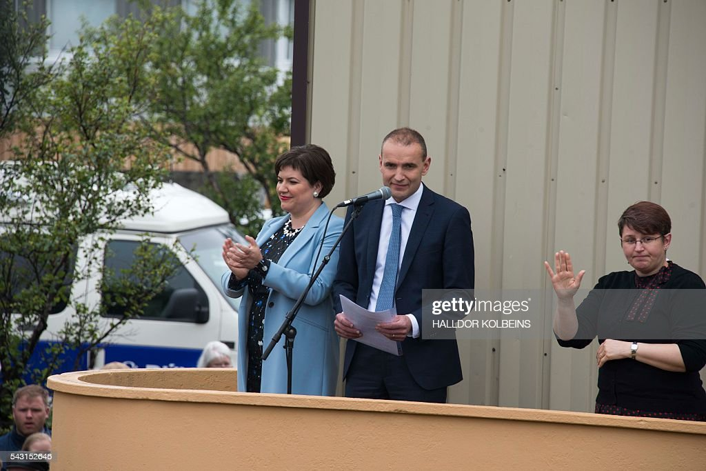 Newly elected president Gudni Johannesson (C) celebrates with his his wife and family in front of his home in Reykjavik, on June 26, 2016. Political newcomer Gudni Johannesson claimed victory in Iceland's presidential election after riding a wave of anti-establishment sentiment, though the vote was eclipsed by the country's eagerly-anticipated and historic Euro football match. / AFP / HALLDOR