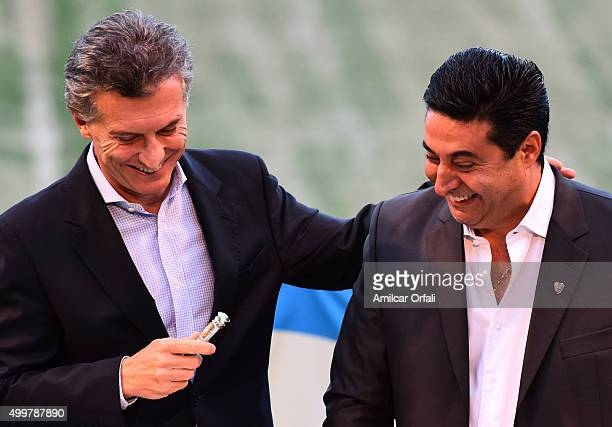 Newly elected President of Argentina Mauricio Macri receives a replica of the presidential baton from Daniel Angelici President of Boca Juniors...
