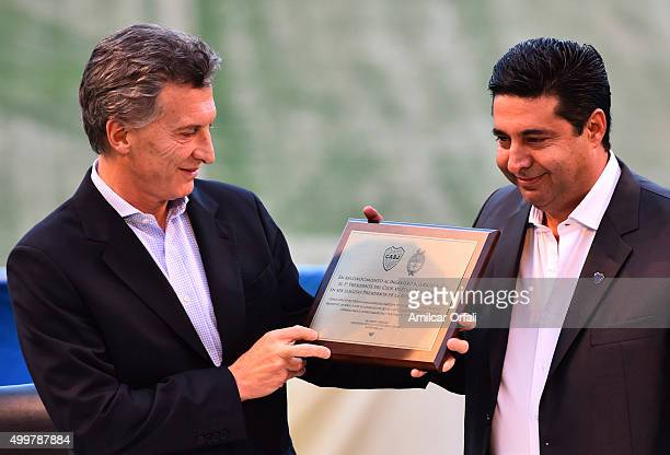 Newly elected President of Argentina Mauricio Macri shows an Honorary Degree delivered by Daniel Angelici President of Boca Juniors during a ceremony...