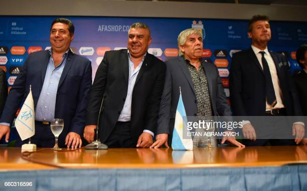 Newly elected President of Argentina's Football Association Claudio Tapia poses next to Boca Juniors' president Daniel Angelici Independiente's...