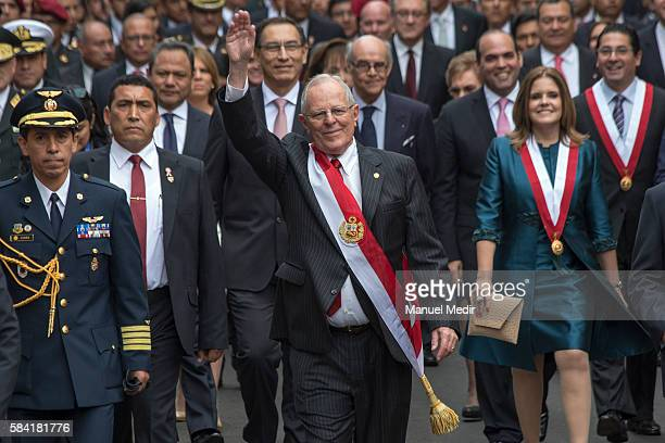 Newly elected President of Peru Pedro Pablo Kuczynski greets supporters as he walks along with his cabinet towards Palacio de Gobierno after the...