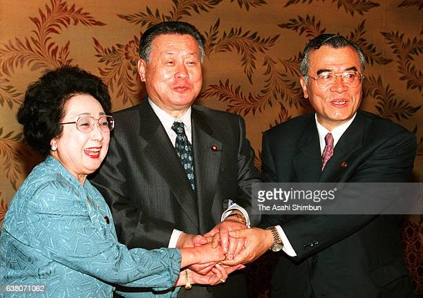 Newly elected Prime Minister and Liberal Democratic Party president Yoshiro Mori shake hands with New Conservative Party leader Chikage Ogi and New...