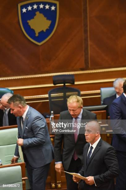 Newly elected Prime Minister of Kosovo Ramush Haradinaj walks past new members of the Kosovo government during a parliament session in Pristina on...