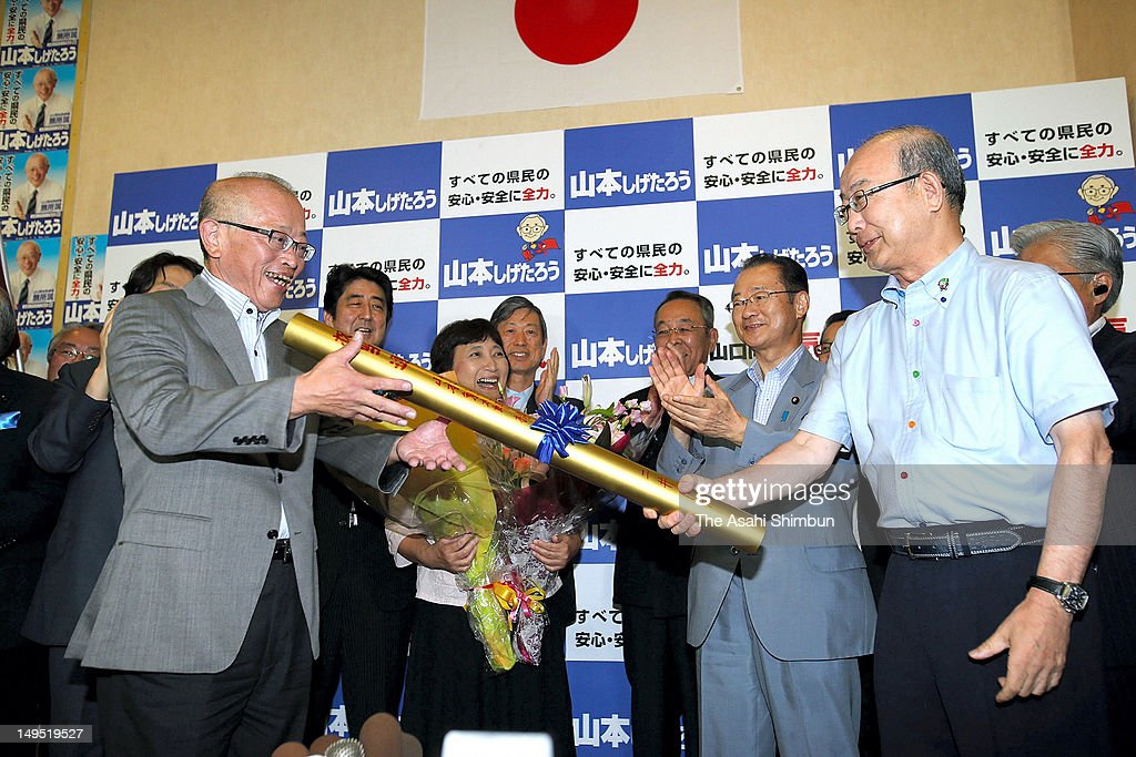 Newly elected Yamaguchi Prefecture Governor Shigetaro Ymamoto (L) is passed the golden baton from outgoing governor Sekinari Nii (R) after winning in the Yamaguchi gubernatorial election at his campaign headquarters on July 29, 2012 in Yamaguchi, Japan.