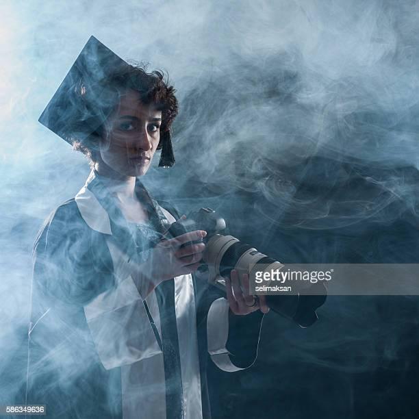 Newly Graduate Female Journalist Holding Camera In Fog