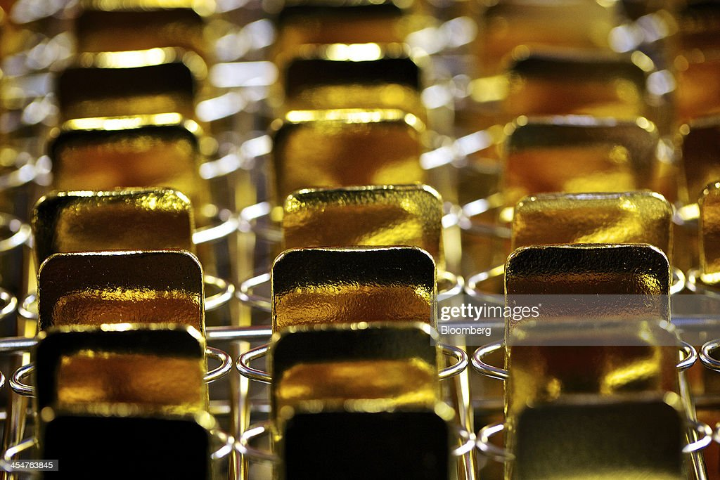 Newly manufactured gold bars sit in storage racks ahead of stamping at a precious metal refinery near Mendrisio Switzerland on Thursday Nov 21 2013...