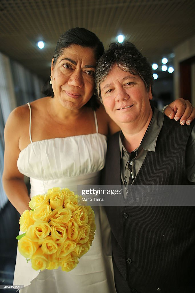 Newly married couple Ana Cristina Ribero Martins (R) and Claudia Almeida Martins, together 23 years, pose at what was billed as the world's largest communal gay wedding on December 8, 2013 in Rio de Janeiro, Brazil. 130 couples were married at the event which was held at the Court of Justice in downtown Rio. In May, Brazil became the third country in Latin America to effectively approve same-sex marriage via a court ruling, but a final law has yet to be passed.