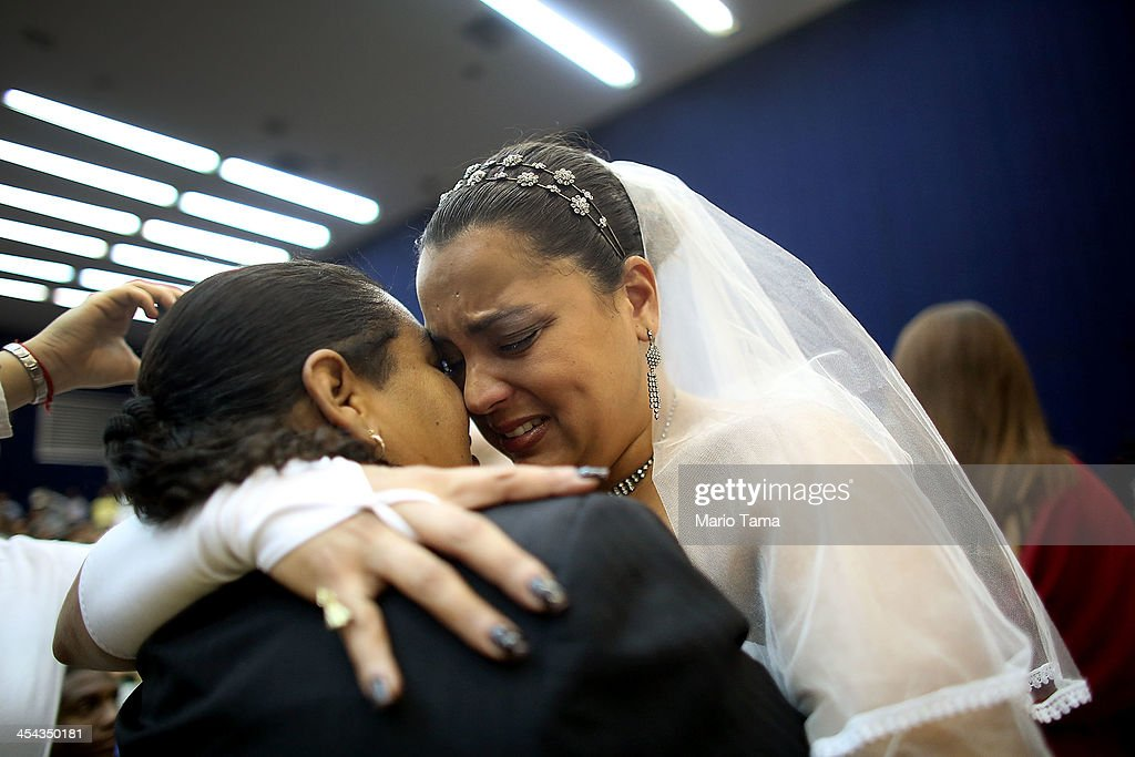 Newly married couple Ana Paula and Juliana (L) react at what was billed as the world's largest communal gay wedding on December 8, 2013 in Rio de Janeiro, Brazil. 130 couples were married at the event which was held at the Court of Justice in downtown Rio. In May, Brazil became the third country in Latin America to effectively approve same-sex marriage via a court ruling, but a final law has yet to be passed.