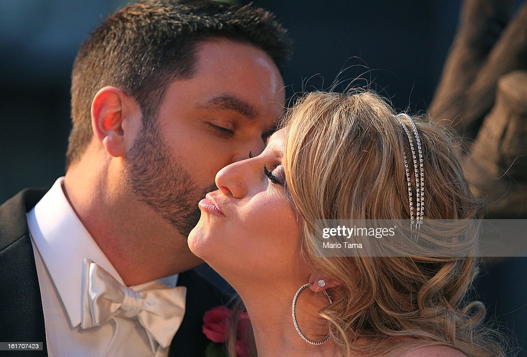 Newly married couple Brian Bondy and Melissa Cohn kiss while posing in Times Square on Valentine's Day on February 14, 2013 in New York City. Bondy proposed to Cohn on 'Good Morning America' this morning and the couple then had a 'flash wedding' in Times Square.