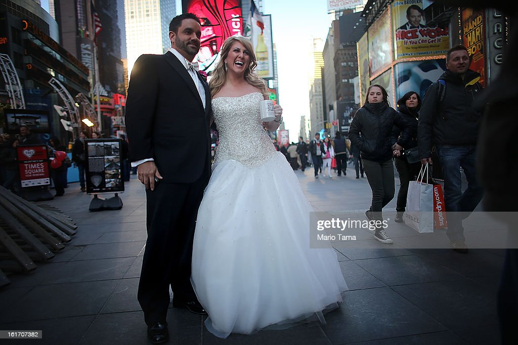 Newly married couple Brian Bondy and Melissa Cohn smile while posing in Times Square on Valentine's Day on February 14, 2013 in New York City. Bondy proposed to Cohn on 'Good Morning America' this morning and the couple then had a 'flash wedding' in Times Square.