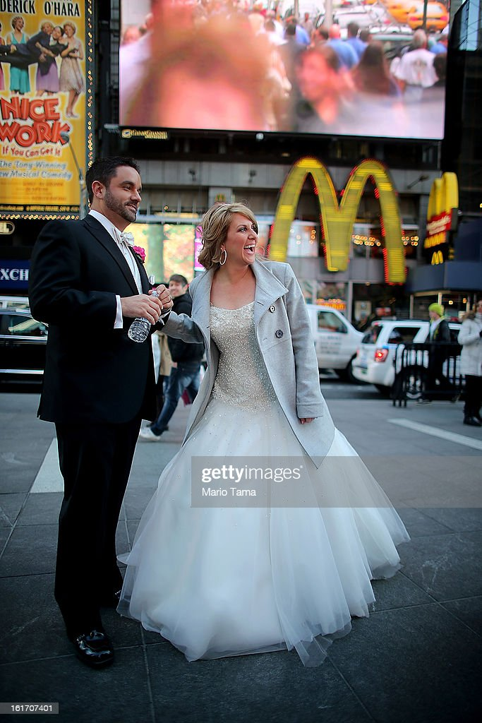 Newly married couple Brian Bondy and Melissa Cohn stand in Times Square on Valentine's Day on February 14, 2013 in New York City. Bondy proposed to Cohn on 'Good Morning America' this morning and the couple then had a 'flash wedding' in Times Square.