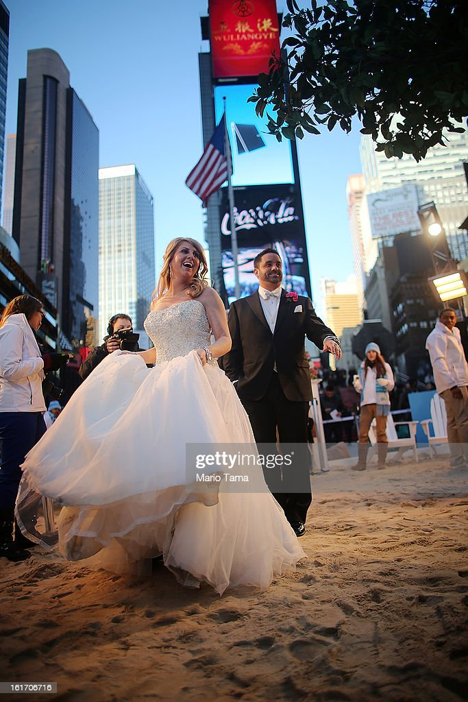 Newly married couple Brian Bondy and Melissa Cohn stand on a mock heated beach in Times Square after being photographed on Valentine's Day on February 14, 2013 in New York City. Bondy proposed to Cohn on 'Good Morning America' this morning and the couple then had a 'flash wedding' in Times Square. The mock heated beach was set up by the Aruba Tourism Authority to promote vacations to the Caribbean island during Valentine's Day celebrations in Times Square.