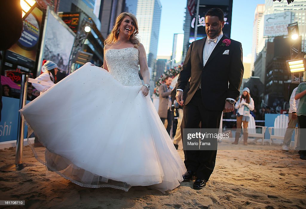 Newly married couple Brian Bondy and Melissa Cohn walk on a mock heated beach in Times Square after being photographed on Valentine's Day on February 14, 2013 in New York City. Bondy proposed to Cohn on 'Good Morning America' this morning and the couple then had a 'flash wedding' in Times Square. The mock heated beach was set up by the Aruba Tourism Authority to promote vacations to the Caribbean island during Valentine's Day celebrations in Times Square.