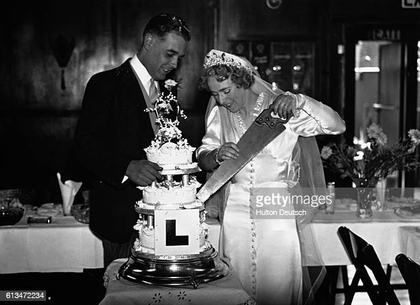 A newly married couple cut into their wedding cake with a large saw