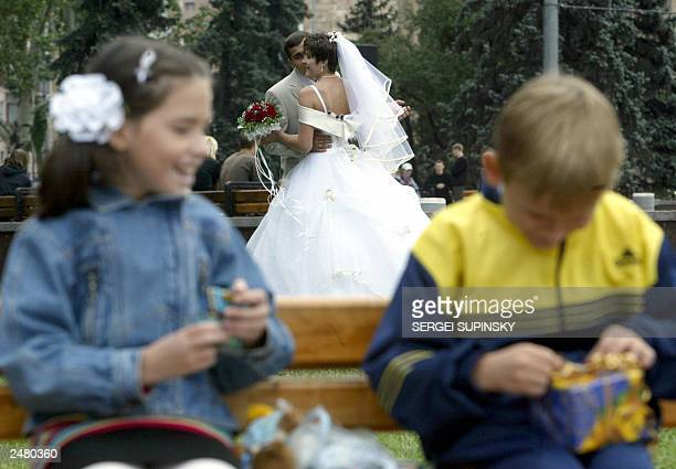 A newly married couple dances in Donetsk eastern Ukraine 07 September 2003 while boy and girl unwrap boxes with sweets AFP PHOTO/ Sergei SUPINSKY/ss