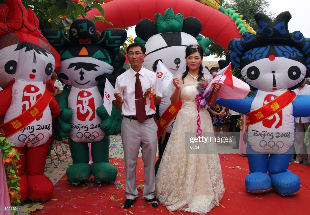 A newly married couple hold the Chinese and Olympic flags flanked by the Olympics mascots during their marriage ceremony on August 8 2008 in Wudi...