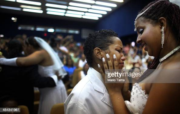 Newly married couple Joyce and Gabrieli embrace at what was billed as the world's largest communal gay wedding on December 8 2013 in Rio de Janeiro...