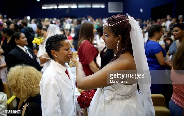 Newly married couple Joyce and Gabrieli react at what was billed as the world's largest communal gay wedding on December 8 2013 in Rio de Janeiro...