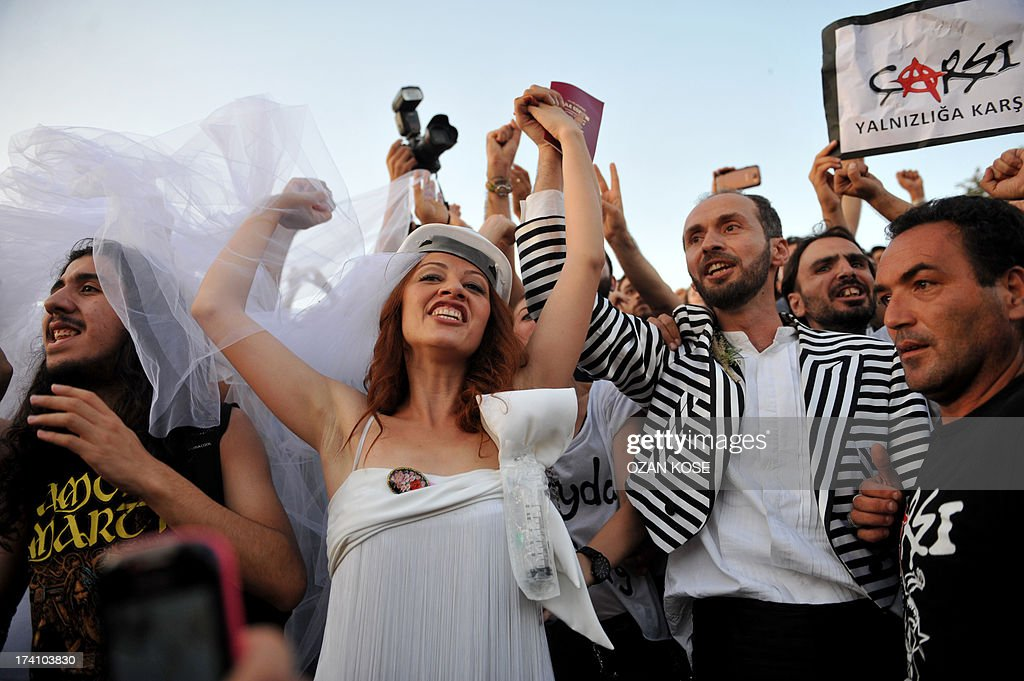 Newly married couple Nuray (L) and Ozgur chant slogans in Gezi Park on July 20, 2013 in Istanbul after being married at the Sisli district's municipal building. Turkish riot police blocked access to Gezi Park ahead of the wedding for the couple that met during the first wave of Gezi protests and had planned to symbolically tie the knot at the park, before firing water cannons at the crowd gathered for the event. AFP PHOTO / OZAN KOSE