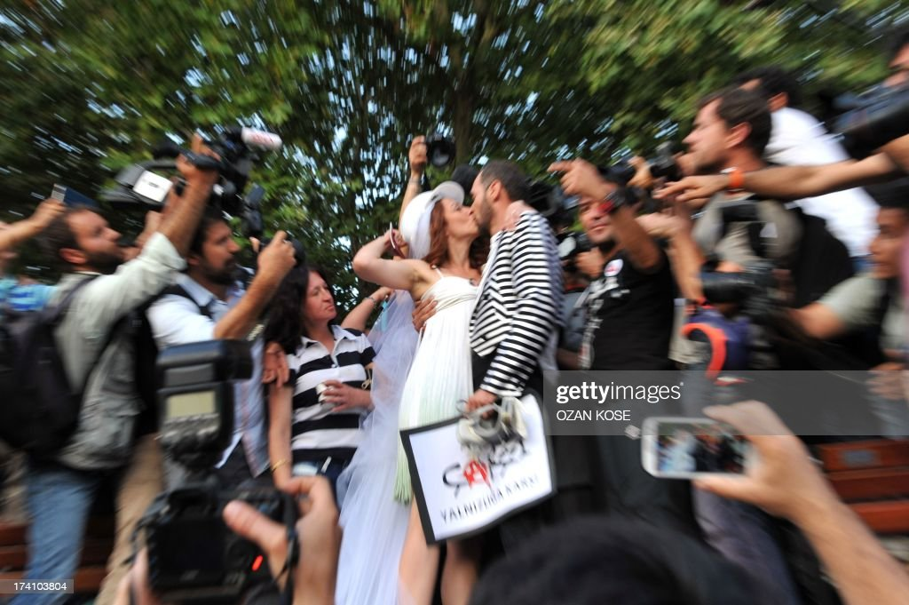 Newly married couple Nuray (L) and Ozgur kiss in Gezi Park on July 20, 2013 in Istanbul after being married at the Sisli district's municipal building. Turkish riot police blocked access to Gezi Park ahead of the wedding for the couple that met during the first wave of Gezi protests and had planned to symbolically tie the knot at the park, before firing water cannons at the crowd gathered for the event.