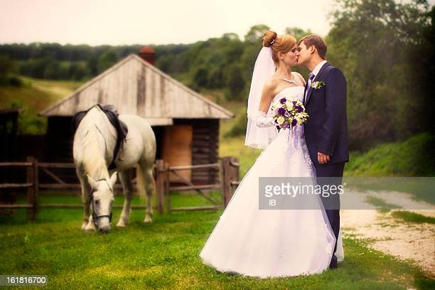 Newly married couple on a farm near grazing horse