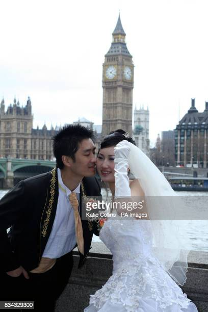 A newly married couple pose for photographs on the South Bank London