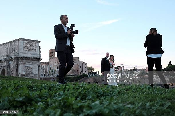 A newly married couple poses for wedding pictures near the Arch of Constantine in Rome on October 17 2015 The city of Rome will soon open up public...
