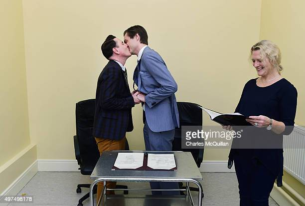 Newly married couple Richard Dowling and Cormac Gollogly kiss next to registrar Mary Clare Heffernan after the first ever same sex marriage takes...