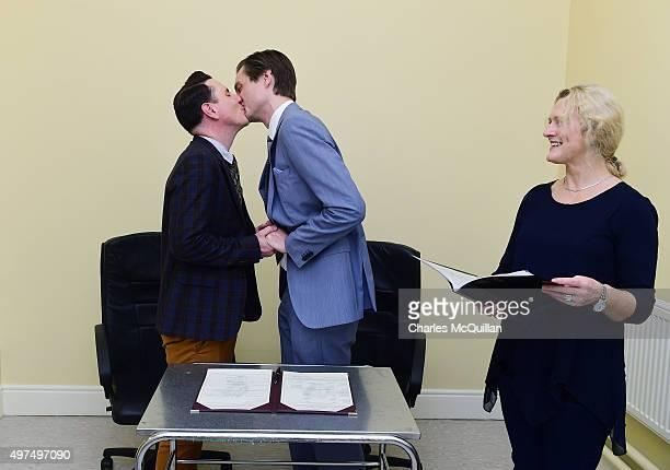 Newly married couple Richard Dowling and Cormac Gollogly kiss watched by registrar Mary Clare Heffernan after the first ever same sex marriage takes...