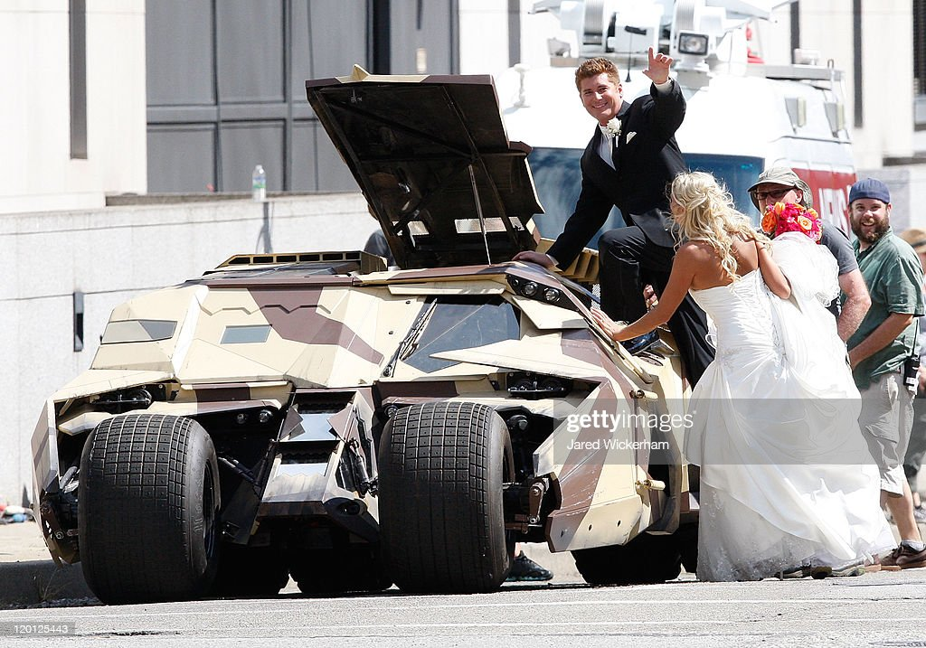 A newly married couple waves to the crowd after being allowed to view the Tumbler after their wedding at a church across the street from the set of 'The Dark Knight Rises' filming near the Carnegie Mellon University Software Engineering Institute Building in the neighborhood of Oakland on July 30, 2011 in Pittsburgh, Pennsylvania.