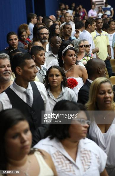 Newly married couples line up to be photographed on stage at what was billed as the world's largest communal gay wedding on December 8 2013 in Rio de...