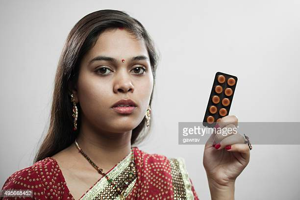 Newly married Hindu young woman holding sachet of medicine tablets.