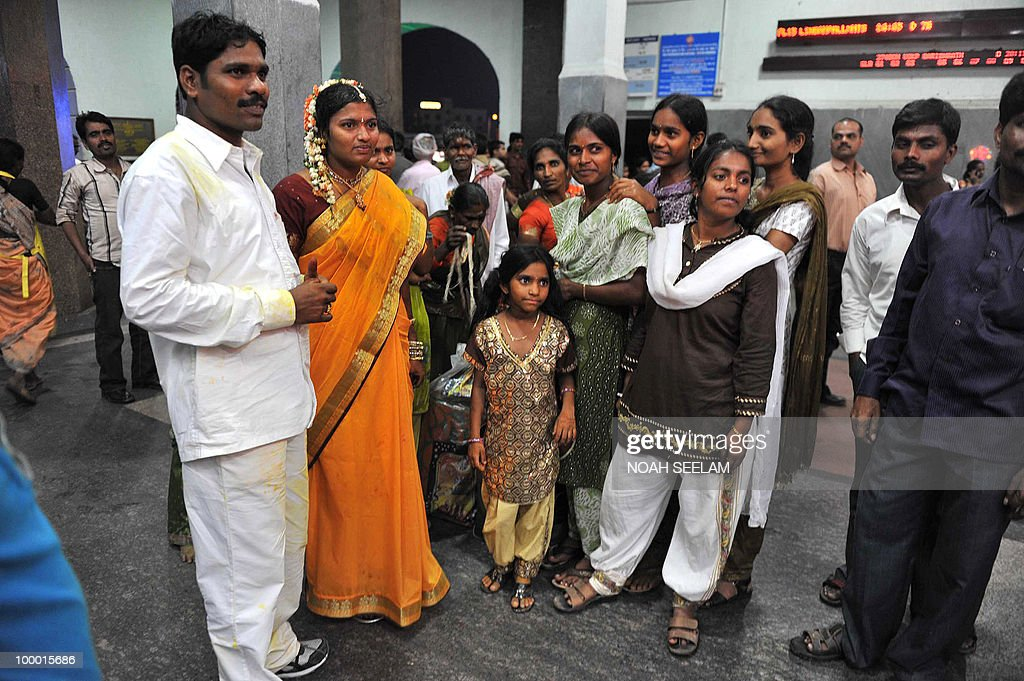 A newly married Indian couple (L) and relatives wait in the Secunderabad Railway station after trains were cancelled in Hyderabad on May 20, 2010. A severe cyclone packing winds of 110 kilometres (70 miles) an hour hit India's southeast coast, forcing tens of thousands of people to evacuate their homes. Cyclone Laila slammed into the state of Andhra Pradesh about 50 kilometres southwest of the city of Machilipatnam, the Indian Meteorological Department (IMD) said. AFP PHOTO/Noah SEELAM