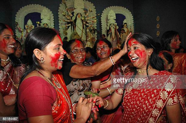 Newly married Indian Hindu women smother each others faces in 'Sindoor' vermillion powder in Ranchi on October 9 on the final day of Durga Puja Durga...