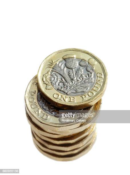Newly minted one pound coins in stack.