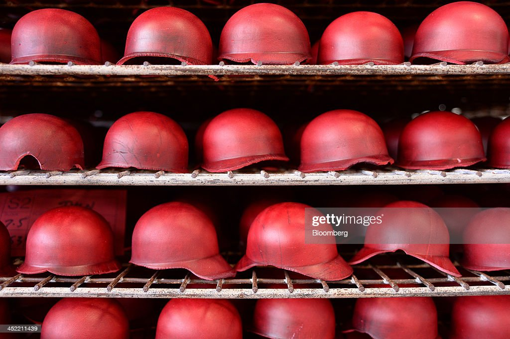 Newly molded leather casings for red cricket balls sit on racks at the Kookaburra Sports Pty Ltd. plant in Melbourne, Australia, on Tuesday, Nov. 26, 2013. Australian businesses need to boost efficiency to maintain growth in living standards, Reserve Bank of Australia Deputy Governor Philip Lowe said. Photographer: Carla Gottgens/Bloomberg via Getty Images
