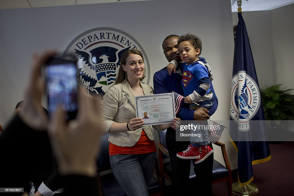 Newly naturalized American citizen Fayick Suleman, from Ghana, center, stands for a photograph his wife Hanadi Suleman, left, and their son Laeyth Suleman, 2, with his certificate of citizenship after a Naturalization Ceremony at the Jacob K. Javits Federal Building in New York, U.S., on Friday, April 19, 2013. A Senate plan to rewrite U.S. immigration law has stoked a years-old debate over allowing undocumented residents a chance to become citizens, a measure viewed by opponents as rewarding lawbreakers with 'amnesty' and undercutting American workers. Photographer: Victor J. Blue/Bloomberg via Getty Images