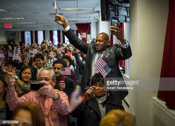 A newly naturalized American citizen stands in celebration during a ceremony at the New York District office of the US Citizenship and Immigration...