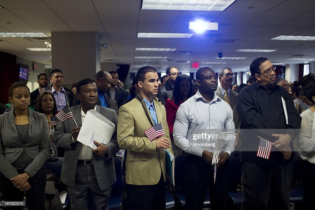 Newly naturalized American citizens stand to take the Oath of Allegiance during a Naturalization Ceremony at the Jacob K. Javits Federal Building in New York, U.S., on Friday, April 19, 2013. A Senate plan to rewrite U.S. immigration law has stoked a years-old debate over allowing undocumented residents a chance to become citizens, a measure viewed by opponents as rewarding lawbreakers with 'amnesty' and undercutting American workers. Photographer: Victor J. Blue/Bloomberg via Getty Images