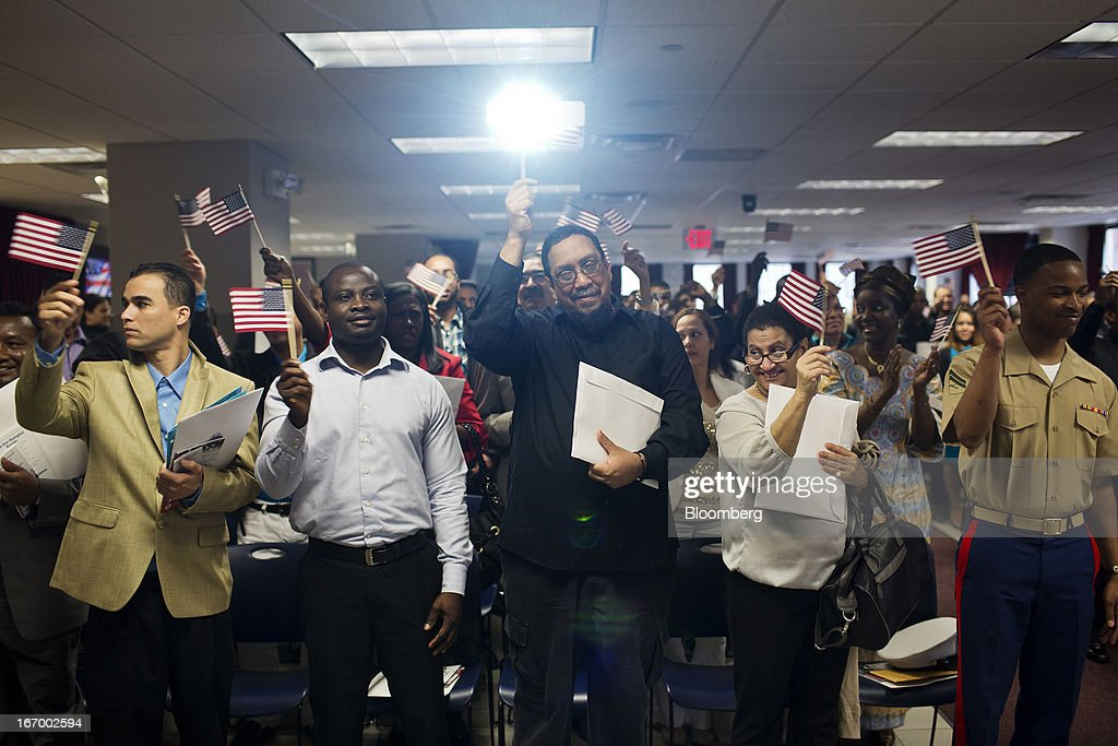 Newly naturalized American citizens take the Oath of Allegiance during a Naturalization Ceremony at the Jacob K. Javits Federal Building in New York, U.S., on Friday, April 19, 2013. A Senate plan to rewrite U.S. immigration law has stoked a years-old debate over allowing undocumented residents a chance to become citizens, a measure viewed by opponents as rewarding lawbreakers with 'amnesty' and undercutting American workers. Photographer: Victor J. Blue/Bloomberg via Getty Images