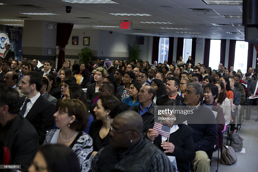 Newly naturalized American citizens wait to take the Oath of Allegiance during a Naturalization Ceremony at the Jacob K. Javits Federal Building in New York, U.S., on Friday, April 19, 2013. A Senate plan to rewrite U.S. immigration law has stoked a years-old debate over allowing undocumented residents a chance to become citizens, a measure viewed by opponents as rewarding lawbreakers with 'amnesty' and undercutting American workers. Photographer: Victor J. Blue/Bloomberg via Getty Images