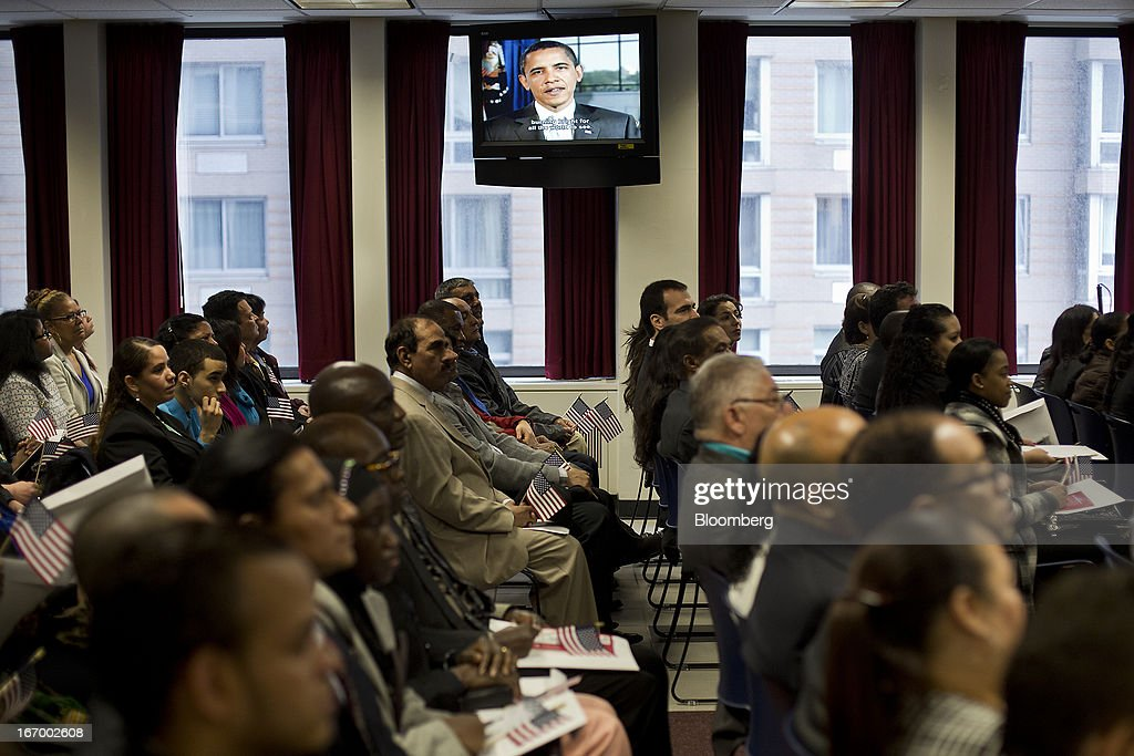 Newly naturalized American citizens watch a video of U.S. President Obama after taking the Oath of Allegiance during a Naturalization Ceremony at the Jacob K. Javits Federal Building in New York, U.S., on Friday, April 19, 2013. A Senate plan to rewrite U.S. immigration law has stoked a years-old debate over allowing undocumented residents a chance to become citizens, a measure viewed by opponents as rewarding lawbreakers with 'amnesty' and undercutting American workers. Photographer: Victor J. Blue/Bloomberg via Getty Images