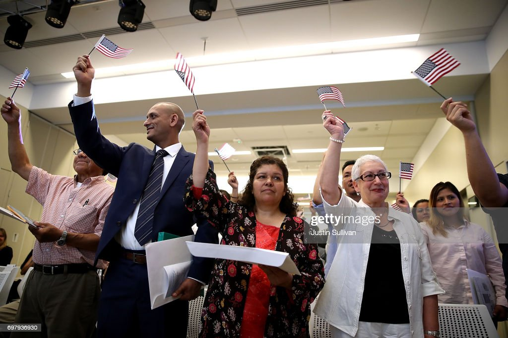 Newly naturalized citizens wave American flags after being sworn in as American citizens during a naturalization ceremony on June 19, 2017 in San Francisco, California. 29 former refugees from 17 different countries were sworn in as Americaan citizens during a ceremony to mark World Refugee Day. World Refugee Day is Tuesday, June 20.