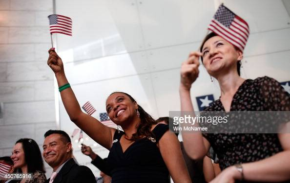 Newly naturalized US citizens Ji Hye Mosher and Sandra Romulus wave American flags after taking the oath of citizenship during a naturalization...