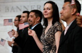 Newly naturalized US citizens wave American flags after taking the oath of citizenship during a naturalization ceremony at the National Museum of...