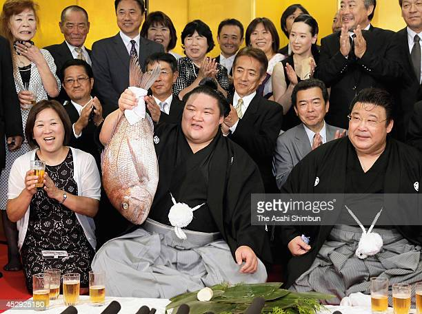 Newly promoted Ozeki second highest rank in sumo Goeido holding a sea bream to celebrate his promotion with his stable master Sakaigawa and his...