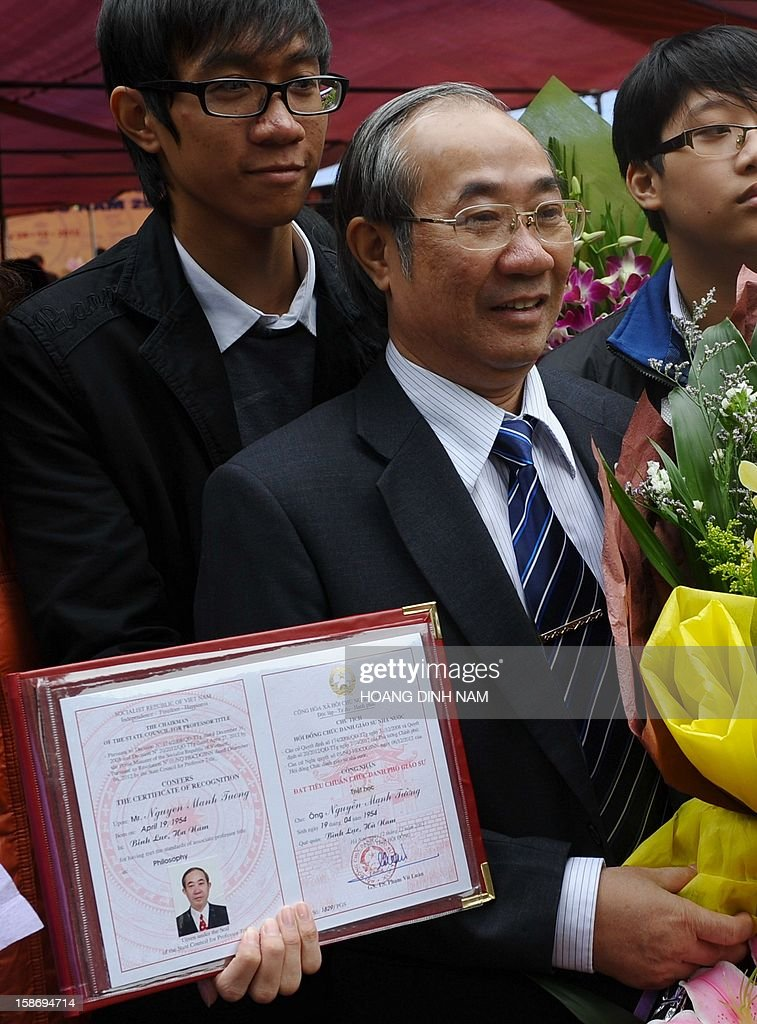 A newly recognised Associate Professor poses with his certificate during a ceremony of confering certificates of recognition for titles of professor and associate professor held at the Temple of Literature in Hanoi on December 24, 2012. This year, some 469 people were confered titles of professor and associate professor. Heavily influenced in the past by Confucian educational philosophy, Vietnam, where society still pays much attention and importance to diplomas and certificates, is known for having a higher number of PhDs than any other ASEAN country but its number of scientific research works published on international journals is smaller. According to official media the Southeast communist nation has not had any patents registered in the US in 2011 despite the country having more than 10,000 professors and associate professors who's qualifications amount to hundreds of thousands of PhD qualifications. AFP PHOTO / HOANG DINH Nam