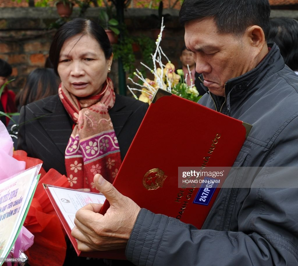 A newly recognised Associate Professor (R) reads a certificate during a ceremony of confering certificates of recognition for titles of professor and associate professor held at the Temple of Literature in Hanoi on December 24, 2012. This year, some 469 people were confered titles of professor and associate professor. Heavily influenced in the past by Confucian educational philosophy, Vietnam, where society still pays much attention and importance to diplomas and certificates, is known for having a higher number of PhDs than any other ASEAN country but its number of scientific research works published on international journals is smaller. According to official media the Southeast communist nation has not had any patents registered in the US in 2011 despite the country having more than 10,000 professors and associate professors who's qualifications amount to hundreds of thousands of PhD qualifications. AFP PHOTO / HOANG DINH Nam